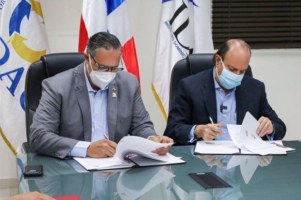 Ángel David Taveras Difo, director ejecutivo de la ODAC y Román E. Caamaño, director general del IDAC, durante la firma del acuerdo interinstitucional.