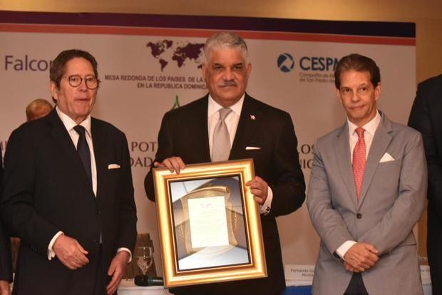 El canciller Miguel Vargas recibe un reconocimiento de Fernando González y José María Cabral.