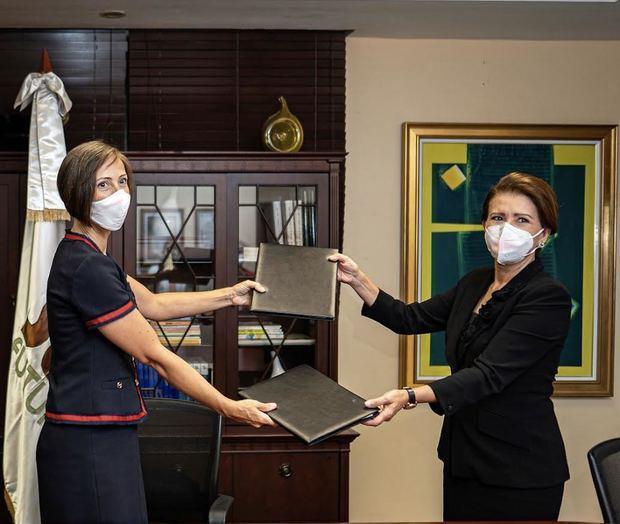 Shauna Hemingway y Melba Segura de Grullón intercambian el acuerdo firmado.