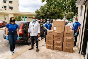 El doctor Felipe Meregildo, administrador del Hospital Robert Reid Cabral, recibe las unidades de gel antibacterial por parte de Vanessa del Villar, gerente de negocios de Laboratorios LAM y personal del laboratorio farmacéutico.
