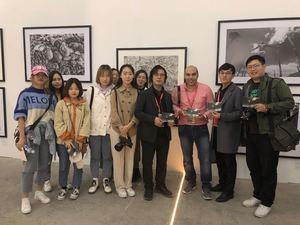 Zhang, curador de la Universidad de las artes de Shadong, muestra junto a sus alumnos, imágenes autografiadas por el fotógrafo dominicano Kelvin Naar.
