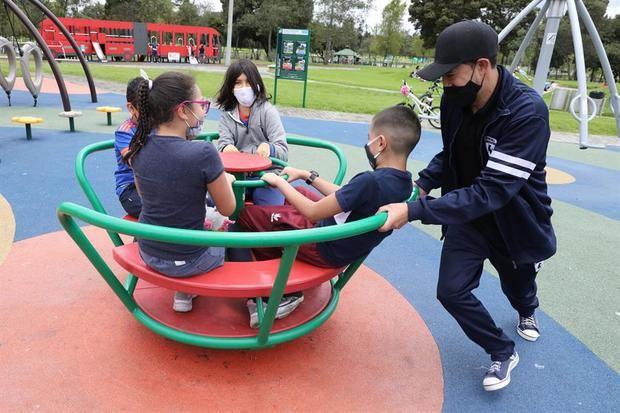 Un grupo de niños, protegidos por mascarillas, juega en el Parque Simón Bolívar de Bogotá, Colombia.