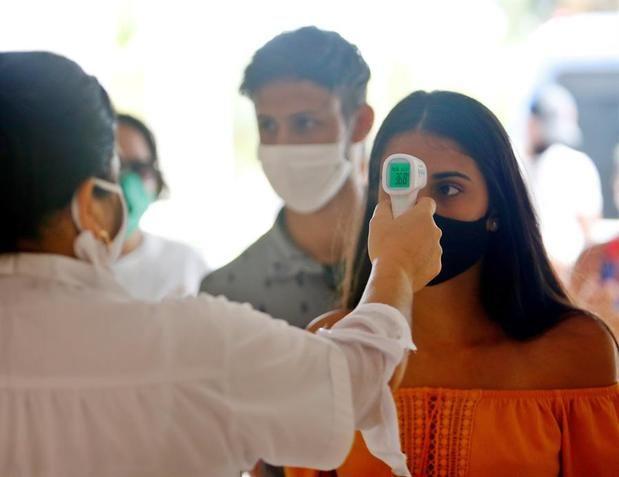 Una trabajadora de la salud toma la temperatura a los visitantes en de Varadero (Cuba).