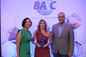July de la Cruz y Armando Rivas entregan el reconocimiento a Mireya Abreu, de Rizek Cacao.