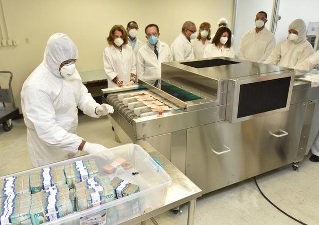 Autoridades del Banco Central dejan en funcionamiento equipo de rayos ultravioleta para desinfección de billetes.