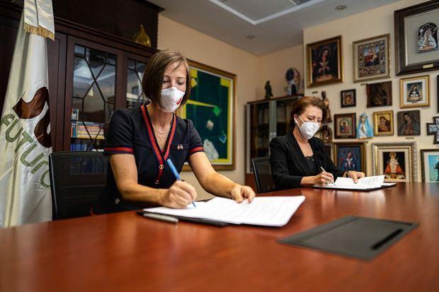 Shauna Heminguay y Melba Segura de Grullón firmando el acuerdo.