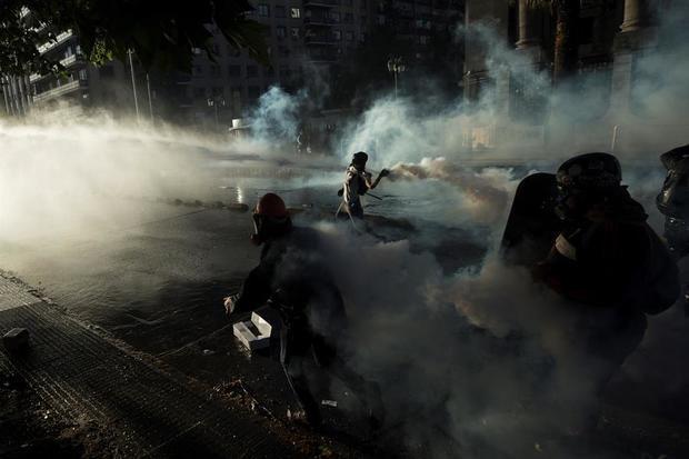Fuerzas Especiales de Carabineros intentan dispersar a manifestantes que se tomaron la Alameda, principal avenida en Santiago, en Chile.