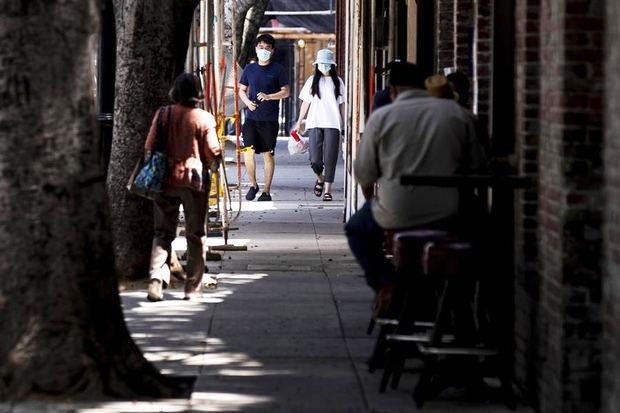 Una pareja camina con tapabocas por una calle de restaurantes en Pasadena, California (EE.UU.), el pasado 14 de julio de 2020.