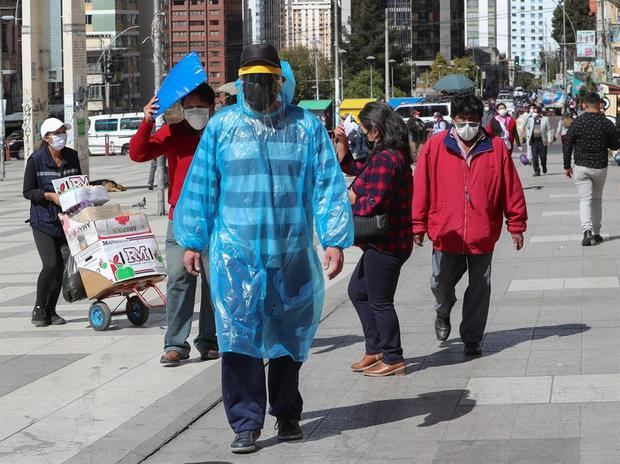 Un hombre camina con una bolsa, tapabocas y careta como medida de protección contra el coronavirus, el pasado 01 de junio del 2020, por las calles de La Paz, Bolivia.