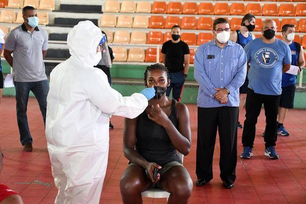 La voleibolista Bethania de la Cruz, al momento en que le toman la muestra. Observa el ministro de Deportes, ingeniero Francisco Camacho.