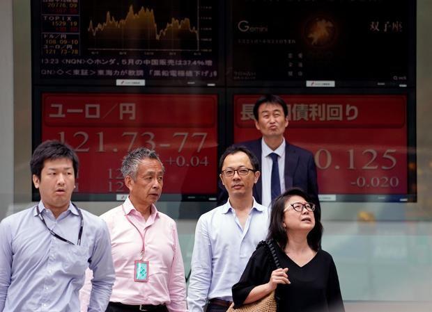 Varios peatones caminan junto a una pantalla que muestra información bursátil en Tokio, Japón.