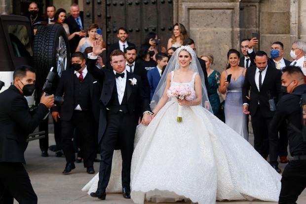 Campeón mundial de peso supermedio de la Asociación Mundial de Boxeo (AMB) y del Consejo Mundial de Boxeo (CMB) Saul 'Canelo' Álvarez y su esposa Fernanda Gómez, saludan hoy, al salir de su boda en la catedral de Guadalajara, estado de Jalisco, México.