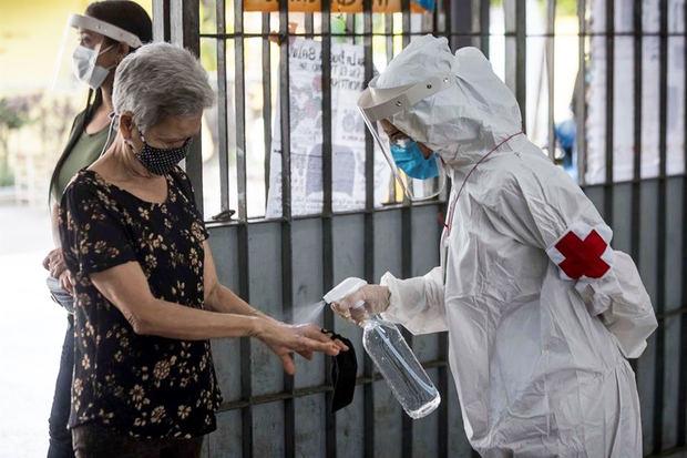 Personal sanitario rocía líquido desinfectante a una mujer.