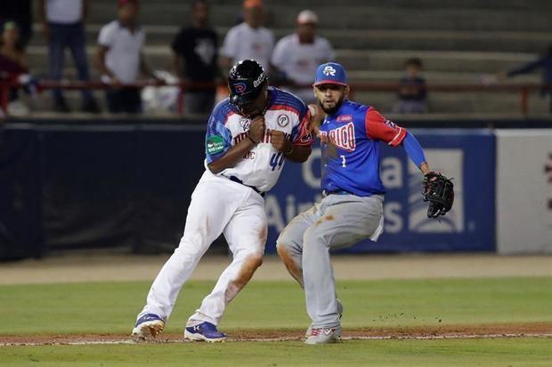 Wilkin Castillo (i) de las Estrellas Orientales de República Dominicana en acción contra Jack Lopez (d) de los Cangrejeros de Santurce de Puerto Rico este jueves, durante un partido de la Serie del Caribe en el estadio nacional Rod Carew en Ciudad de Panamá.