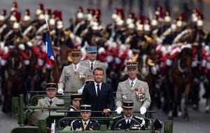 El presidente francés, Emmanuel Macron (c), a bordo del vehículo militar, flanqueado por la Guardia Repulblicana montada, asiste al desfile militar anual del Día de la Bastilla en la avenida de los Campos Elíseos en París, Francia, este 14 de julio.