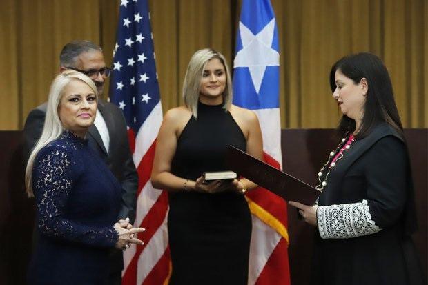 La secretaria de Justicia de Puerto Rico, Wanda Vázquez (i) sonríe este miércoles junto a su esposo, el juez José Díaz Reveron (2-i) y su hija, Beatriz Díaz (c), durante la juramentación como nueva gobernadora de Puerto Rico, ante la jueza presidenta del Tribunal, Maite Oronoz (d), encargada de tomar la juramentación, en San Juan (Puerto Rico).