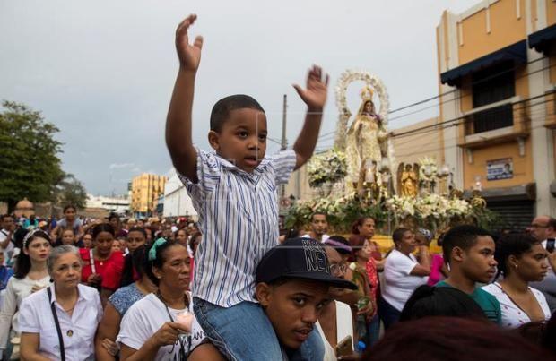 Un niño fue registrado este mates al levantar los brazos, durante la procesión de la Virgen de las Mercedes, patrona del país, en Santo Domingo (República Dominicana)