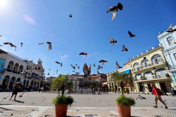 Turistas caminan entre las palomas en una plaza este viernes en La Habana (Cuba). Las autoridades cubanas se suman este viernes a la celebración del Día Mundial del Turismo con estrategias enfocadas a la diversificación de las propuestas de la industria de los viajes y el cuidado del medio ambiente. La isla cuenta con más de 70 mil habitaciones hoteleras en unos 300 establecimientos distribuidos por todo el país.