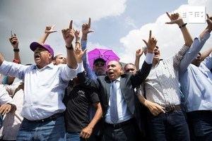 El dirigente Radhamés Jiménez (c) habla ante cientos de seguidores de Leonel Fernández, expresidente de la República y precandidato presidencial del oficialista Partido de la Liberación Dominicana (PLD), que se manifiestan este martes frente a la sede de la Junta Central Electoral para reclamar contra los resultados de las primarias del pasado domingo, en Santo Domingo (República Dominicana).