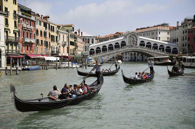 Vista de turistas subidos a góndolas en los canales de Venecia.