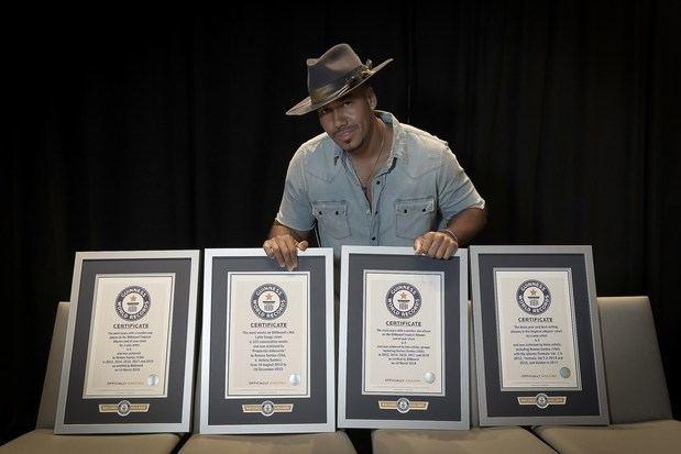 Fotografía sin fecha cedida por Guinness World Records donde aparece el cantante y compositor neoyorquino, Romeo Santos, mientras posa con sus cuatro certificados de récord mundial.