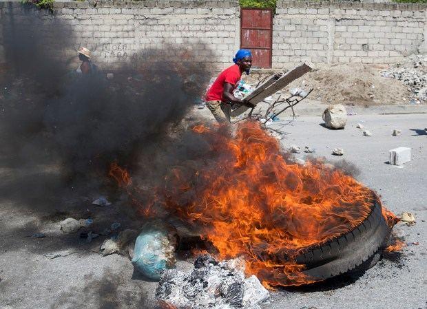 Un hombre aviva una barricada en llamas mientras cientos de seguidores del expresidente haitiano Jean Bertrand Aristide marchan exigiendo la dimisión del actual presidente, Jovenel Moise, este viernes, en Puerto Príncipe (Haití).