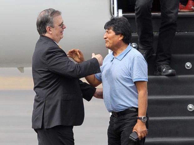 El ministro mexicano de Exteriores, Marcelo Ebrard (i), recibe al expresidente de Bolivia Evo Morales a su llegada este martes al Aeropuerto Internacional de la Ciudad de México (México).