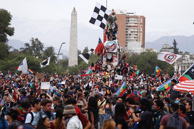 """Miles de manifestantes protestan este lunes, durante una nueva jornada de movilizaciones en el país, a un mes del inicio de las mismas, en la Plaza Italia de Santiago, Chile, rebautizada popularmente como """"Plaza de la Dignidad""""."""