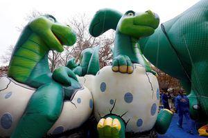 Los trabajadores de globos de Macy's trabajan en el globo 'Dino' un día antes del 93 ° Desfile Anual de Acción de Gracias de Macy's en Nueva York,  EE. UU.