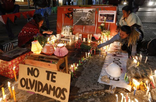 Un grupo de personas enciende velas en el lugar donde el joven estudiante Dilan Cruz recibió un disparo por parte de un miembro de la policía en el marco de una movilización parte del paro nacional, durante la tradicional noche de las velitas que marca en muchas ciudades del país el inicio de la Navidad, este sábado, en la Plaza de Bolívar, en Bogotá (Colombia).