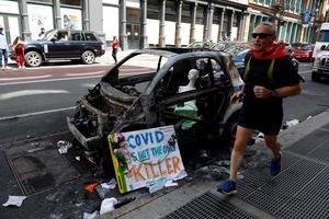 Un hombre trota junto a un auto quemado del Departamento de Policía de la ciudad de Nueva York frente a la tienda de Bloomingdale's en SOHO después de las últimas noches saqueando disturbios como parte de la respuesta de los manifestantes a la muerte de George Floyd, en Nueva York, Nueva York, EE. UU.