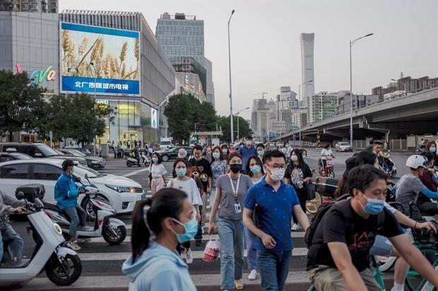 Gente con mascarilla camina por la calle en Pekín, China.