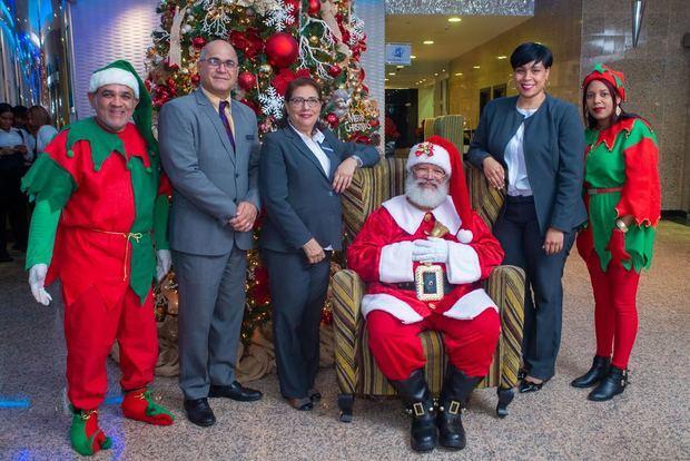 Genaro Santos, Rosario Sangiovani (Charo) Katiuska Méndez, con Santa Claus y su duendes.