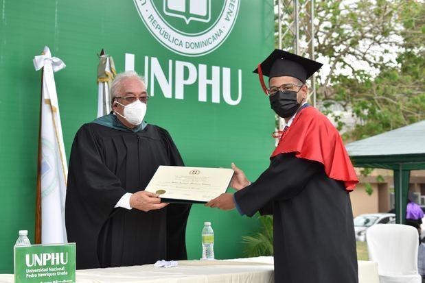 Graduando de la Facultad de Ciencias Jurídicas y Políticas junto al magistrado Juan Biaggi Lama.