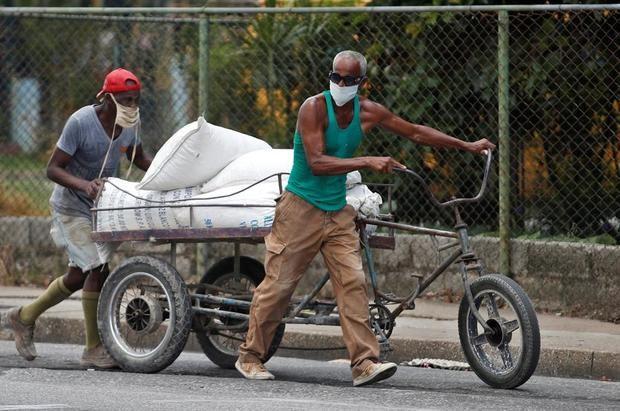 Dos hombres con mascarillas empujan un triciclo con carga por una calle, en La Habana, Cuba.