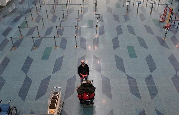 Un hombre con una mascarilla está solo en el aeropuerto internacional de Tokio en Haneda en Tokio, Japón.