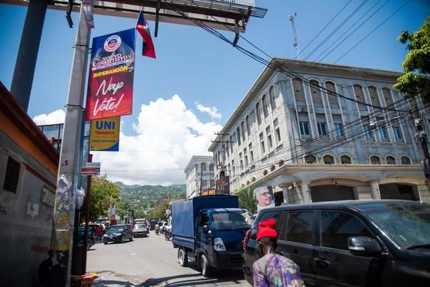 Un ciudadano camina hoy junto a un cartel que convoca a participar del referéndum que impulsa el presidente Jovenel Moise, en Puerto Príncipe, Haití.