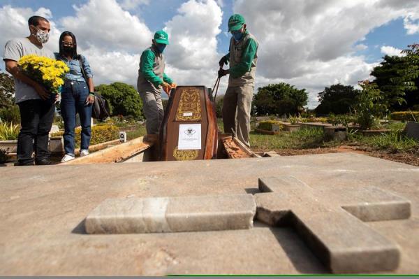 Trabajadores del cementerio Campo de Esperanza entierran una víctima de covid-19 el 3 de junio de 2020 en Brasilia (Brasil).