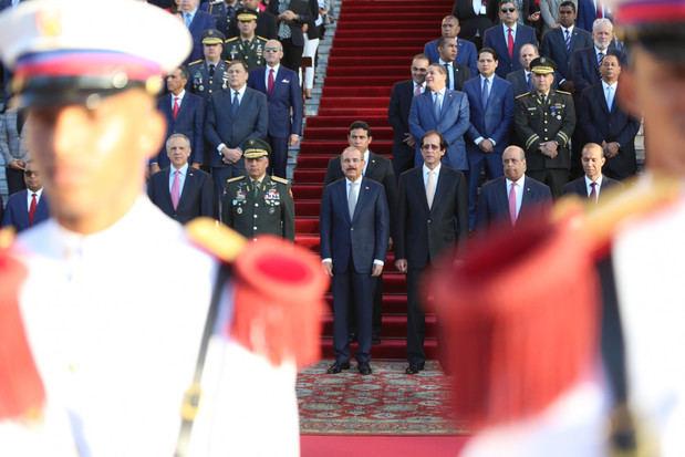 El presidente Danilo Medina, acompañado de ministros, directores generales y otros empleados del Gobierno, rindió un solemne tributo a la Bandera Dominicana, durante una ceremonia realizada en la explanada frontal del Palacio Nacional.