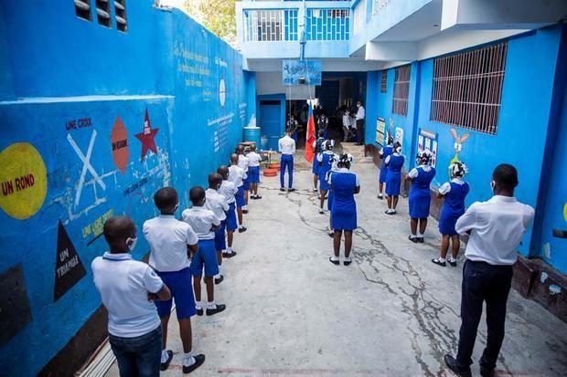 Estudiantes, usando tapabocas, participan de una ceremonia antes de retomar clases luego de cinco meses de cierre debido a la pandemia de coronavirus, este lunes, en Puerto Príncipe (Haití).