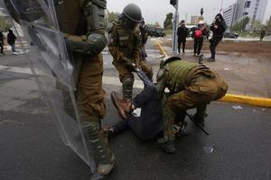 Integrantes de la Policía de Chile (Carabineros) arrestan a un hombre durante una protesta en contra del Gobierno del presidente chileno Sebastián Piñera hoy, en la plaza Italia en Santiago, Chile.