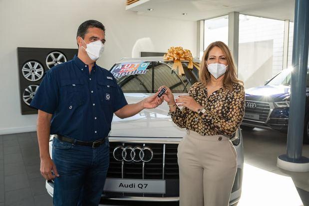 La doctora Evangelina Soler recibe de manos del señor Francisco Ramírez, vicepresidente ejecutivo de Negocios Personales y Sucursales, las llaves del vehículo que adquirió en la Autoferia Popular.