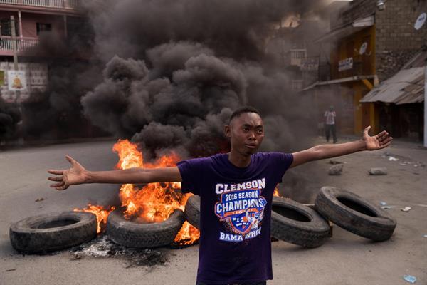 Un hombre camina frente a una pila de llantas en llamas durante una jornada de protestas a la vez que se rindieron homenajes al asesinado presidente Jovenel Moise,
