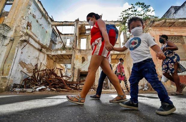 Varias personas caminan por la calle usando mascarillas para protegerse del coronavirus, este sábado, en La Habana, Cuba.