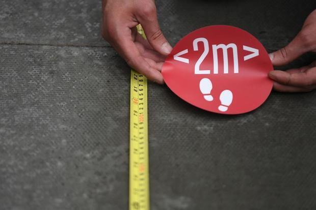 Un cartel de distancia social de dos metros se coloca en Oxford Street en Londres, Gran Bretaña.