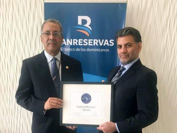 El representante de LatinFinance, Taimur Admad, entrega al administrador general de Banreservas, Simón Lizardo Mézquita, el premio otorgado por la revista a la institución financiera, durante la Asamblea Anual de FELABAN, celebrada en Miami.