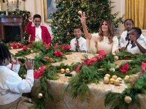 La primera dama de EE.UU., Melania Trump juega con un niño invitado a ver los adornos de la Casa Blanca lanzándole uno de los globos de la decoración.