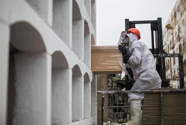 Un trabajador empuja un féretro hacia una tumba el pasado 25 de mayo del 2020 durante su funeral en el cementerio El Ángel en Lima, Perú.