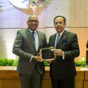 Ervin Novas Bello recibe su placa de reconocimiento por cumplir 30 años en el BCRD, le entrega el gobernador, Héctor Valdez Albizu.