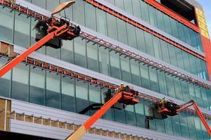 Trabajadores de la construcción realizan sus labores en la fachada de un edificio.